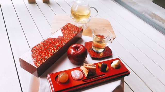 津軽塗りのお菓子箱の中に並ぶりんごスイーツたちの写真